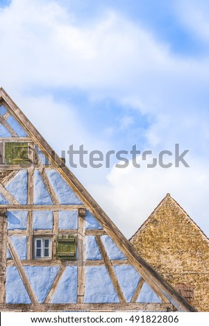 Details of medieval german gable roofs - Medieval architecture background with two german gable roofs, one house with blue half timbered walls and one with aged stone wall.