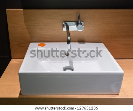 Details of modern square ceramic sink and faucet tap in surface mount on wooden surface - stock photo