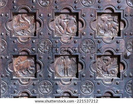 Details of old decorative medieval wooden door - stock photo