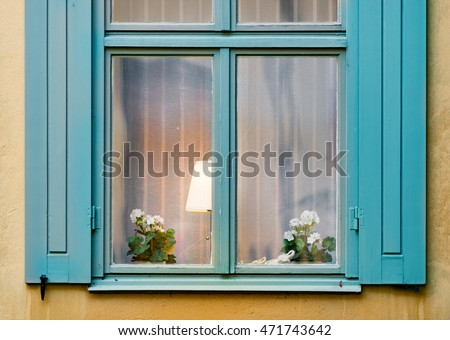 Details of old house window with flower and lamp inside. Yellow wall of building. Stockholm, Sweden, Scandinavia, Europe.