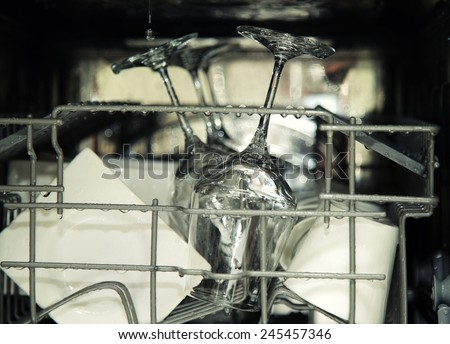 details of open dishwasher, utensils with drops in during washing - stock photo