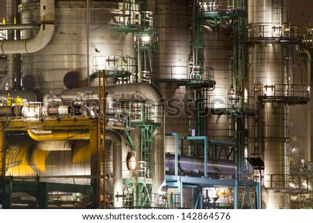 Details of pipes and chimneys of a large oil-refinery plant at night