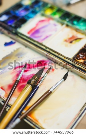 Details of the creative process of the artist, palette with watercolor paints and brushes. School of Art and Drawing Lessons. Soft focus and beautiful bokeh.