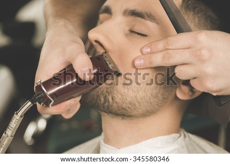 Details of trimming. Cropped closeup of a barber trimming beard to his client - stock photo