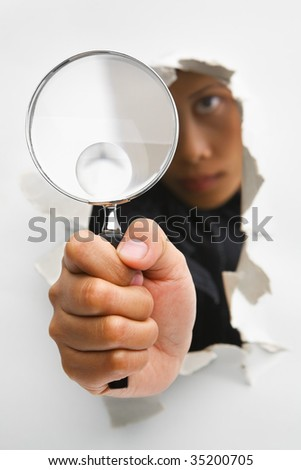 Detective holding magnifying glass from cracked wall means breakthrough in investigation - one of the breakthrough series. PS : focus on the magnifying glass - stock photo