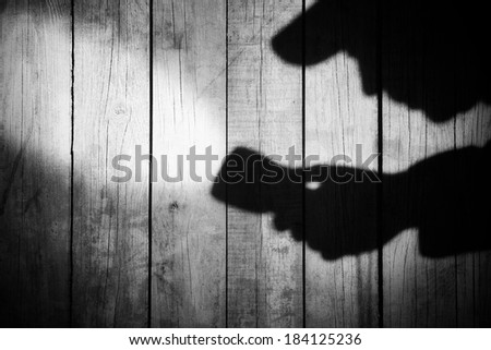 Detective Silhouette with a searchlight on Grungy Wooden Background.  - stock photo