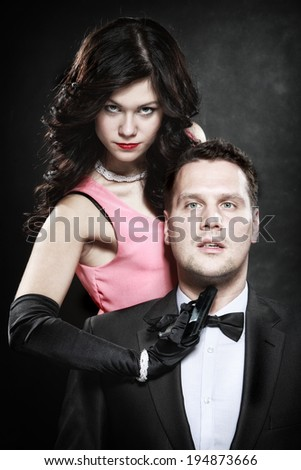 Detective theme. Retro style attractive couple, rich gangster and charming woman sexy detective spy with gun on black background - stock photo