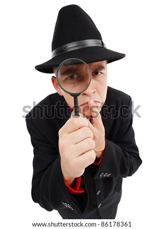 Detective with big hat, thumb on mouth, looking through magnifying glass seriously - stock photo