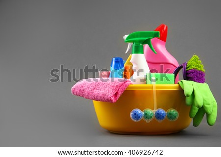 Detergent bottles and cleaning supplies in a bowl - stock photo