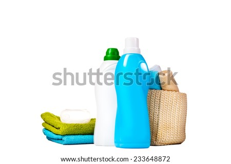 Detergent in blue and white plastic bottles with fresh towels and measuring cup isolated on white background. Bottle with liquid laundry detergent, cleaning agent, bleach or fabric softener. - stock photo