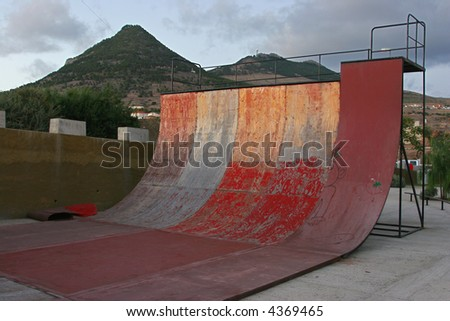 deteriorated skate half pipe at sunset