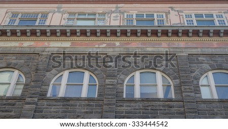 Deteriorating building with shades of former glory in tones of gray/grey and sandstone, for use as an advertising backdrop. - stock photo