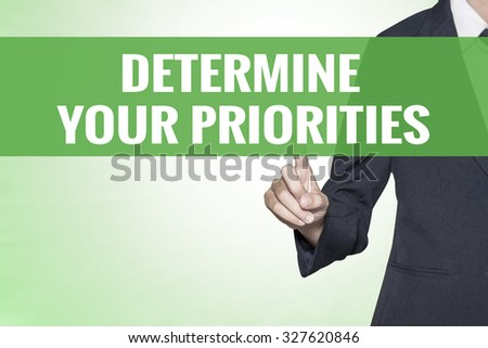 Determine Your Priorities word on green virtual screen touching by business woman - stock photo