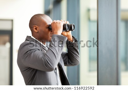 determined african american businessman using binoculars in office - stock photo