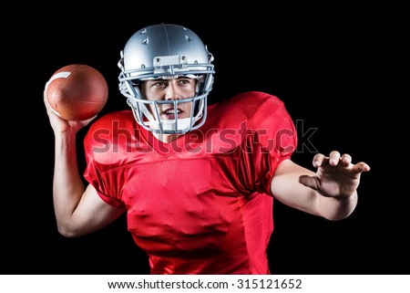 Determined American football player throwing ball against black background