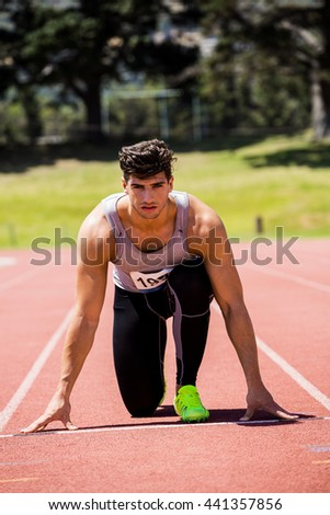 Determined athlete ready to run on running track - stock photo
