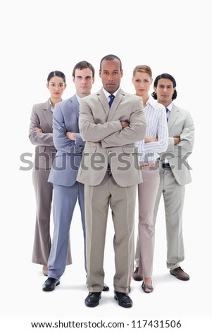Determined business team crossing their arms against white background - stock photo
