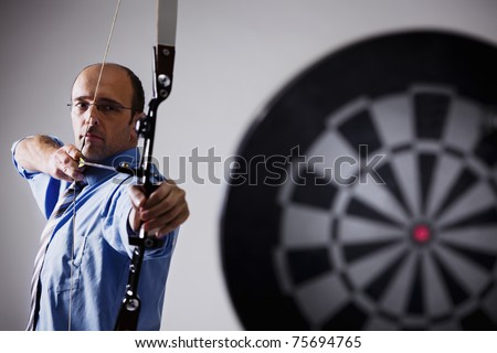 Determined businessman aiming at target with bow and arrow, isolated on white background. - stock photo