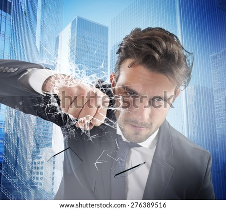 Determined businessman breaks the glass with punch - stock photo