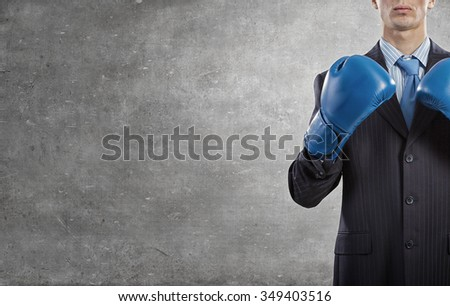 Determined businessman in suit and boxing gloves - stock photo