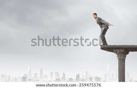 Determined businessman jumping in deep from edge of building