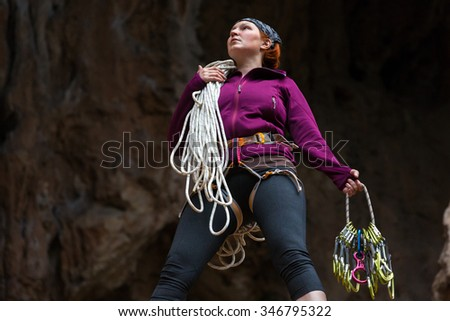 Determined Cute Female Climber holding rope and gear watching up on dark rock background - stock photo