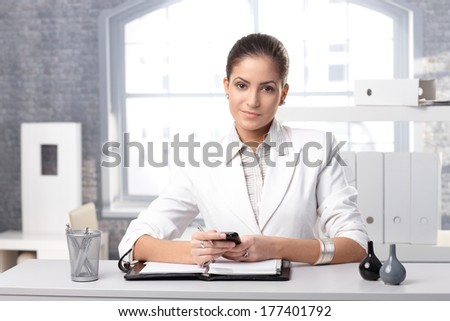 Determined elegant businesswoman at desk using mobile phone and personal organizer. - stock photo