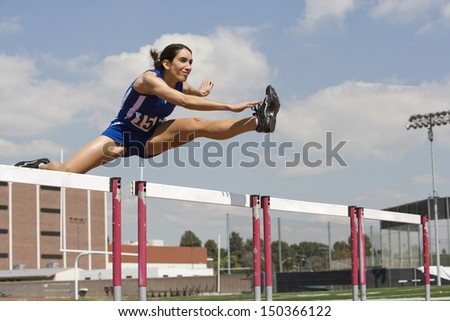 Determined female athlete jumping over a hurdles - stock photo
