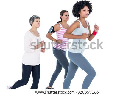 Determined female friends jogging against white background - stock photo