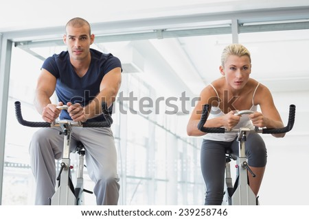 Determined fit young couple working on exercise bikes at the gym - stock photo