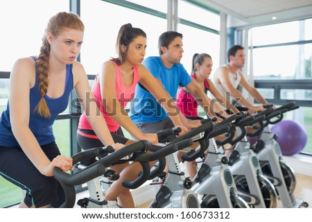 Determined five people working out at an exercise bike class in gym