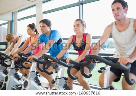 Determined five people working out at class in gym - stock photo