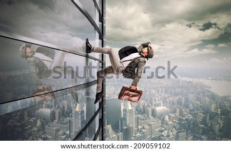 Determined man running up a skyscraper - stock photo