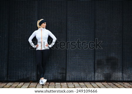 Determined woman resting after jogging in the city. Full length shot of sporty young woman relaxing after running exercise. - stock photo