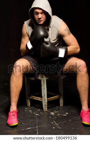 Determined young boxer sitting on a wooden stool waiting for a fight leaning forwards with his gloved fists raised staring at the camera - stock photo