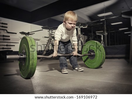 Determined young boy trying to lift a heavy weight bar - stock photo