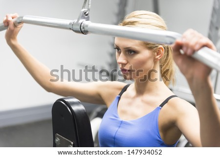 Determined young woman exercising with pulley in gym - stock photo