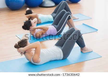 Determined young women doing sit ups in row at the fitness studio
