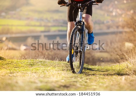 Detial of cyclist man legs riding mountain bike on outdoor trail in nature - stock photo