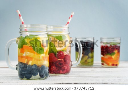 Detox drinks with fresh fruits and berries in glass jars on blue background - stock photo