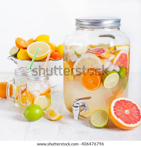 Detox fruit infused flavored water, lemonade, cocktail in a beverage dispenser with fresh fruits Cleanse body and burn fat - stock photo