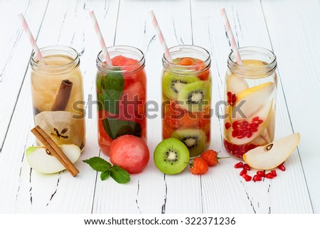 Detox fruit infused flavored water. Refreshing summer homemade cocktail. Clean eating - stock photo