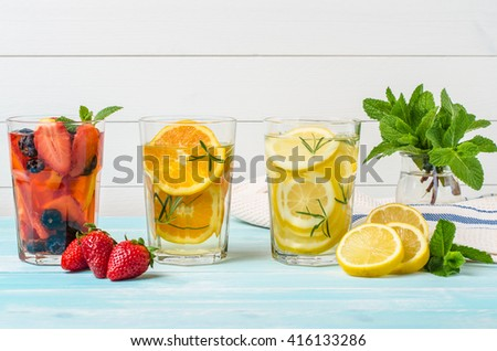 Detox fruit infused flavored water. Refreshing summer homemade cocktail with strawberries, blueberries, orange, lemon and mint leaves - stock photo