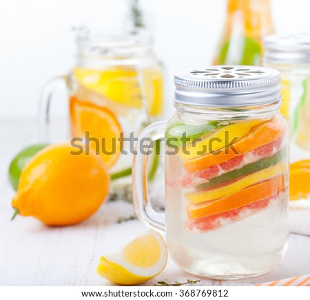 Detox fruit infused flavored water. Refreshing summer homemade lemonade cocktail Cleanse body and burn fat - stock photo