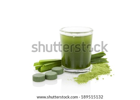 Detox. Green dietary supplement spirulina, chlorella and wheatgrass pills, grass blades and green juice isolated on white background. Healthy living.  - stock photo