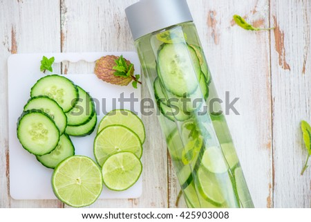 Detox Infused Water with Cucumber, Lime and Mint in Sports Bottle, with cut pieces of cucumber and lime nearby