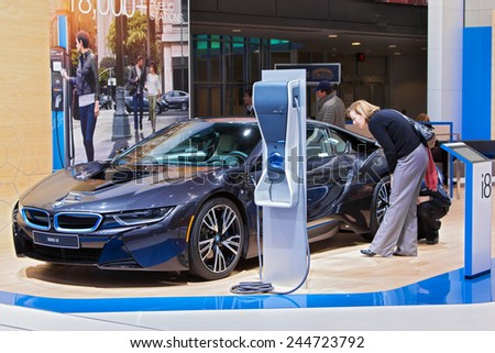 DETROIT - JANUARY 15: A visito looking at the BMW i8 electric vehicle  January 13th, 2015 at the 2015 North American International Auto Show in Detroit, Michigan. - stock photo