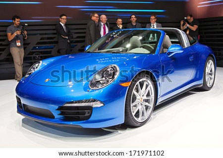 DETROIT - JANUARY 13 : Members of the media examine the new Porsche 911 Targa at the North American International Auto Show media preview  January 13, 2014 in Detroit, Michigan. - stock photo