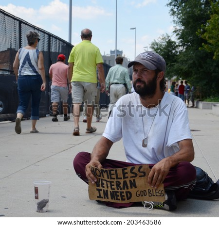 DETROIT, MI - JULY 6: Homeless veteran waits as people walk past him as he begs for money in Detroit, MI on July 6, 2014 - stock photo