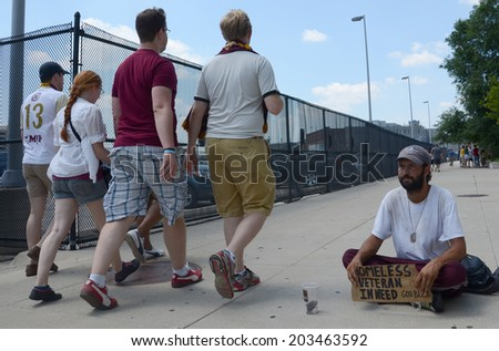 DETROIT, MI - JULY 6: People walking past homeless veteran begging for money in Detroit, MI on July 6, 2014 - stock photo